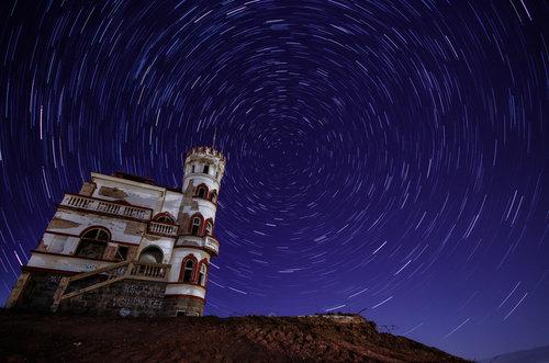 VuckoBre Star trails above abandoned castle